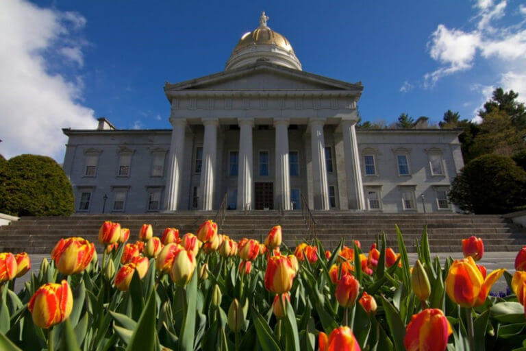 Vermont Statehouse building with red and yellow tulips lining the front of the building