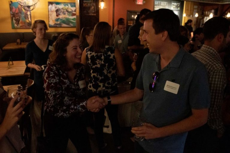 photo of two young professionals shaking hands and wearing nametags at recent byp event